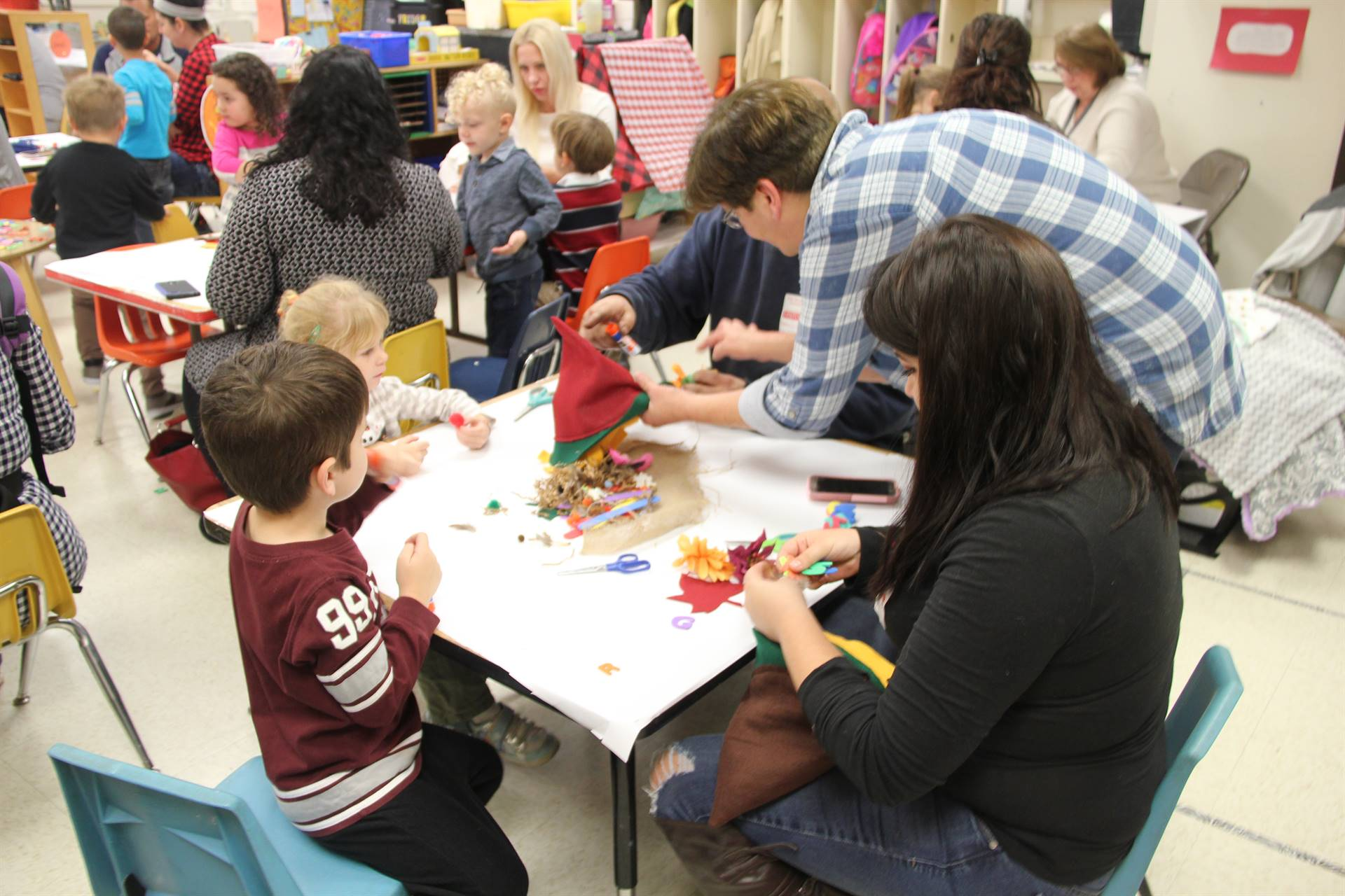 people working on making scarecrow hats at pre k family day