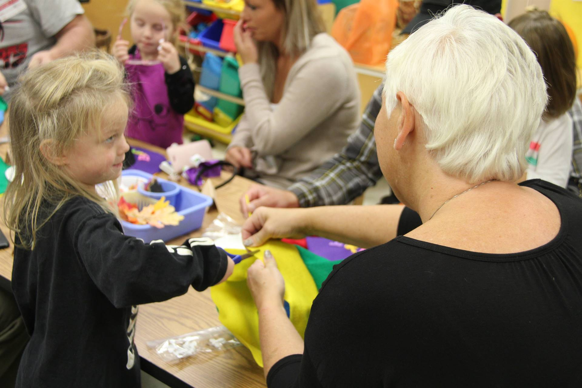 woman holds felt scarecrow hat while pre k student cuts it