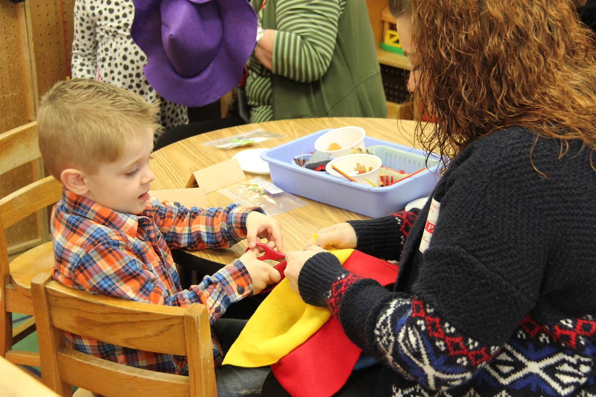 woman holds scarecrow hat while boy cuts with scissors