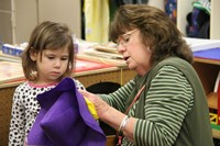 woman works with girl to make a purple scarecrow hat