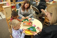 women helping children make hats at pre k family day