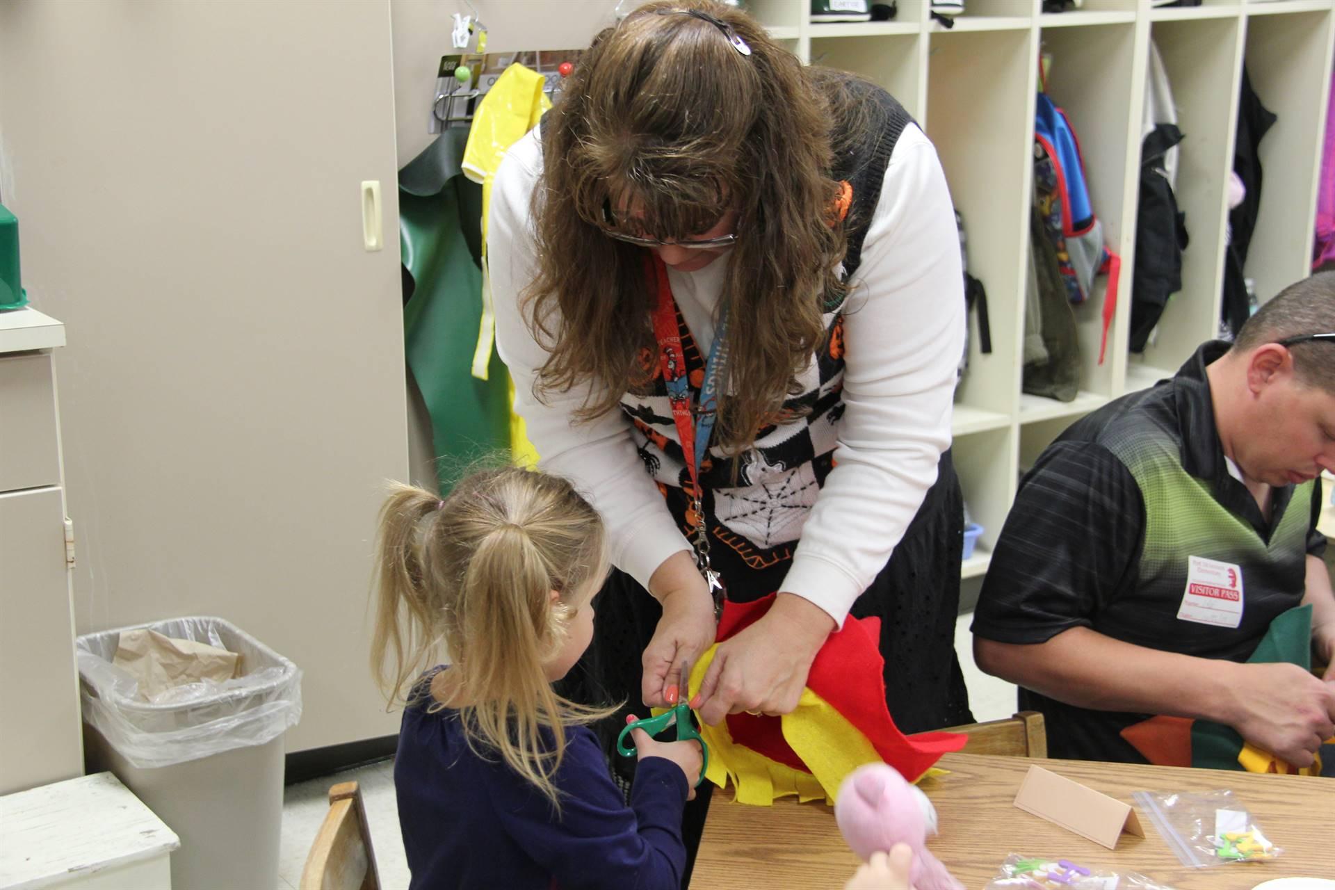 woman helping girl cut felt scarecrow hat