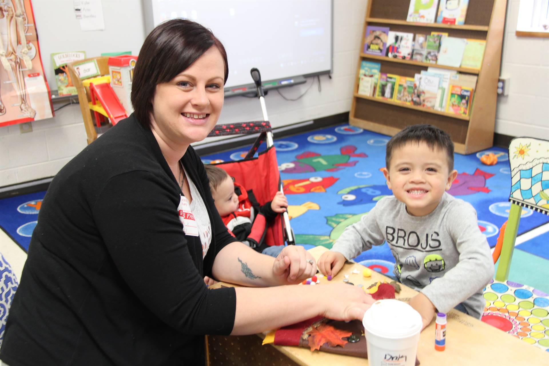 woman and student smile for a picture at pre k family day