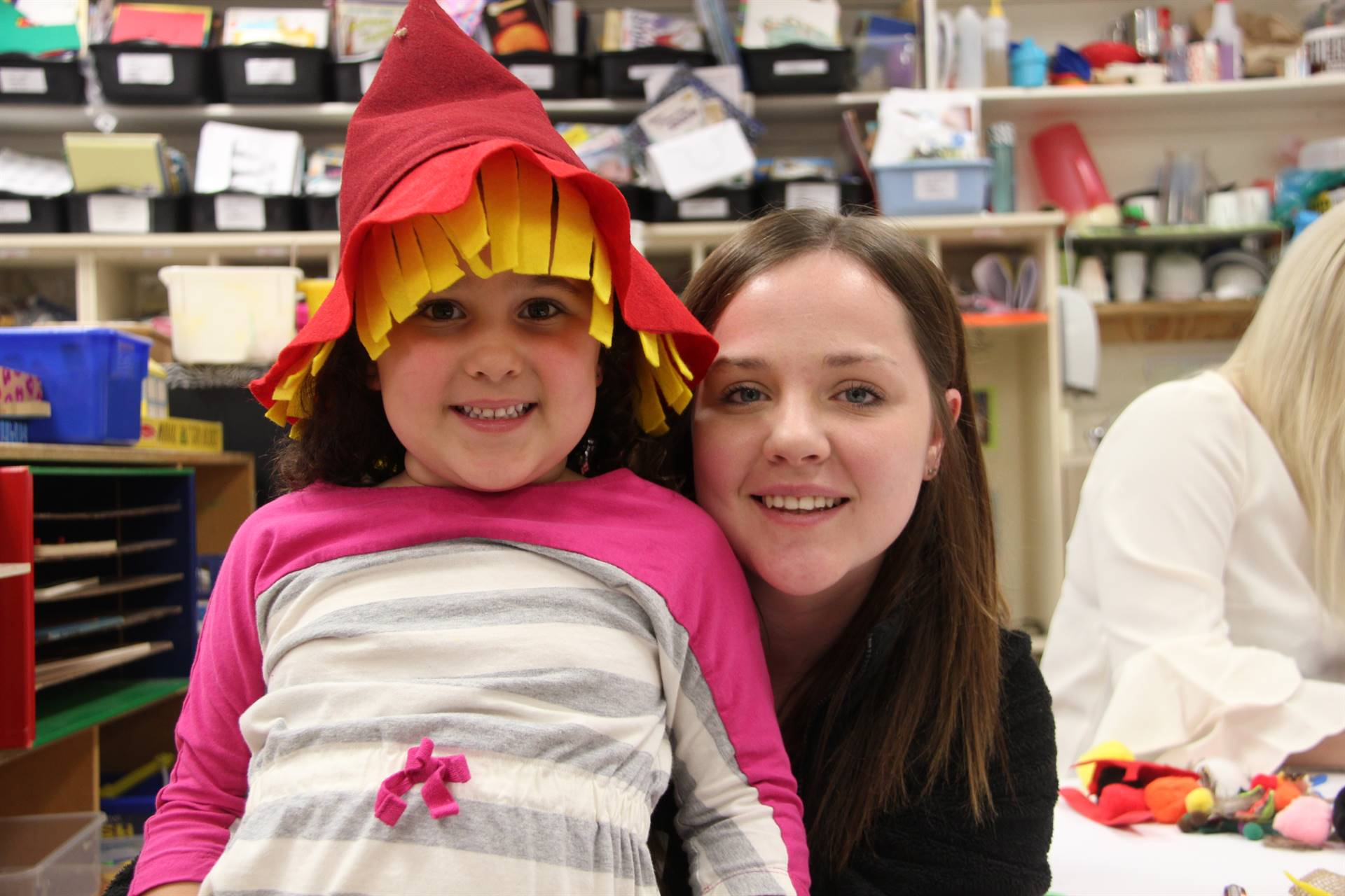 woman and girl who is wearing scarecrow hat smiling