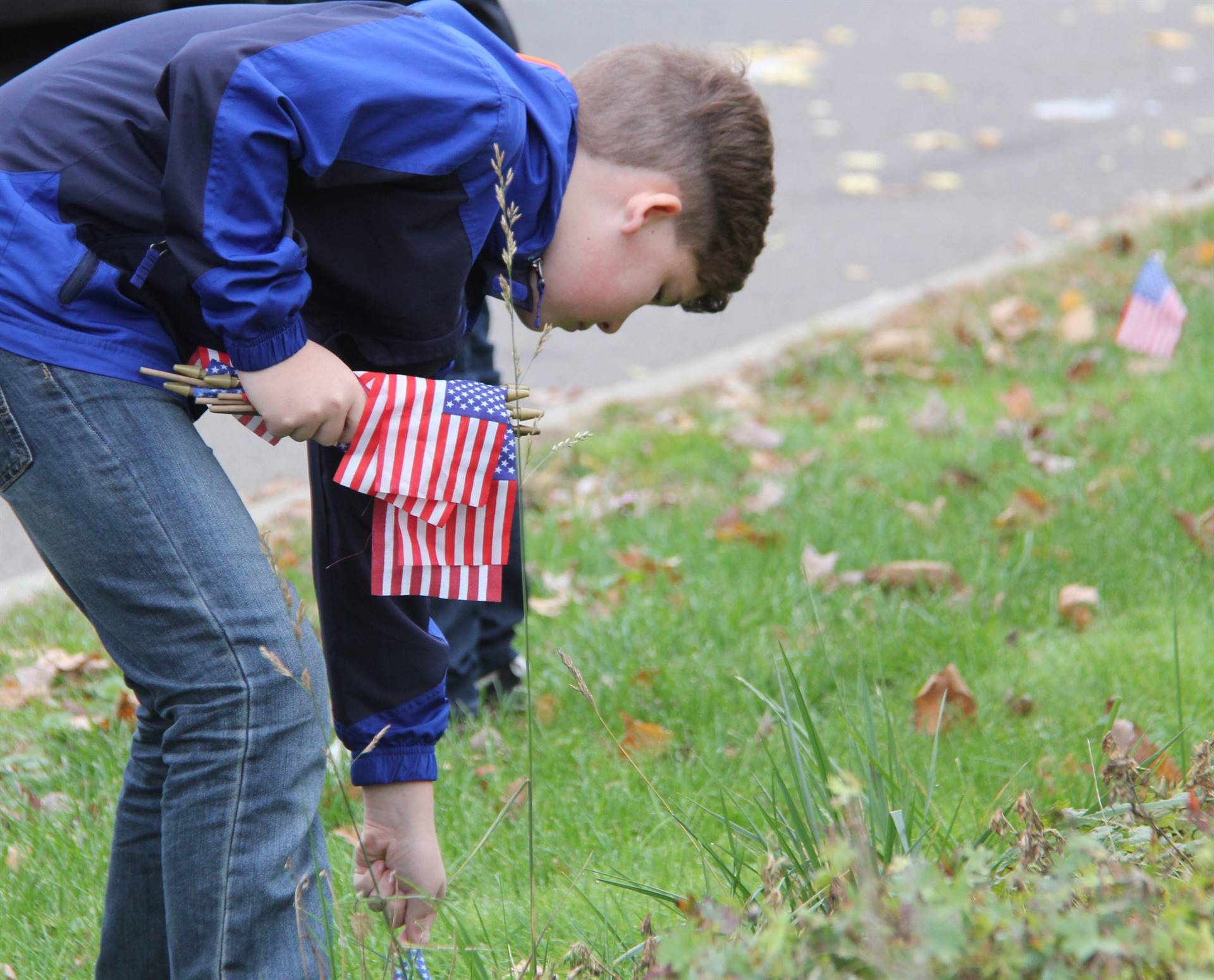 student placing small american flag in ground