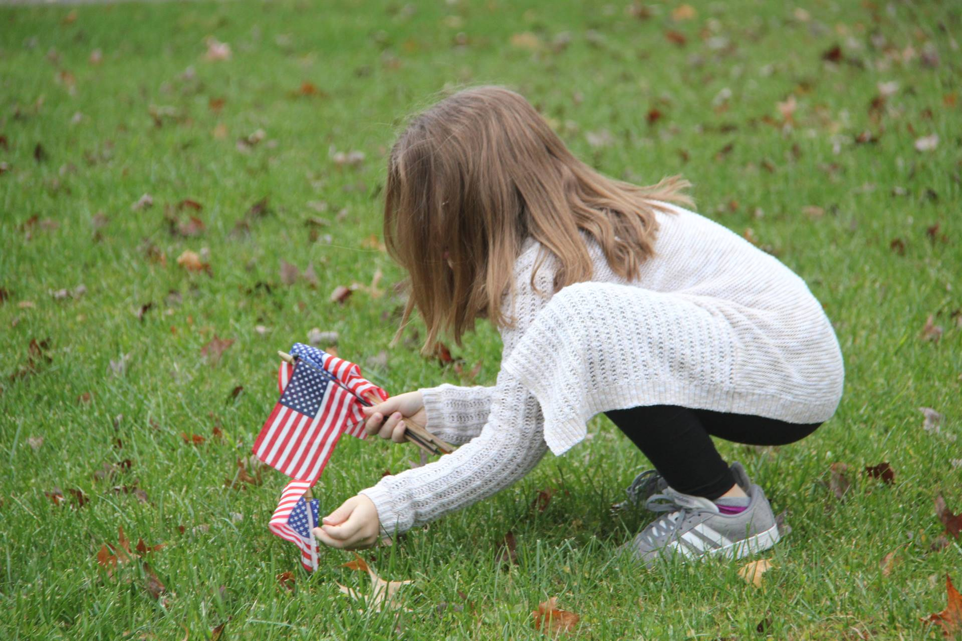 student placing small american flag in grass