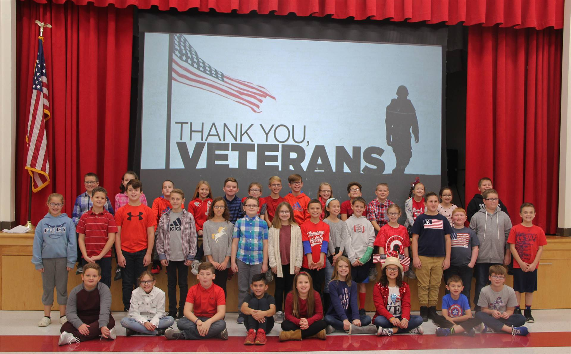 students in front of thank you veterans power point slide