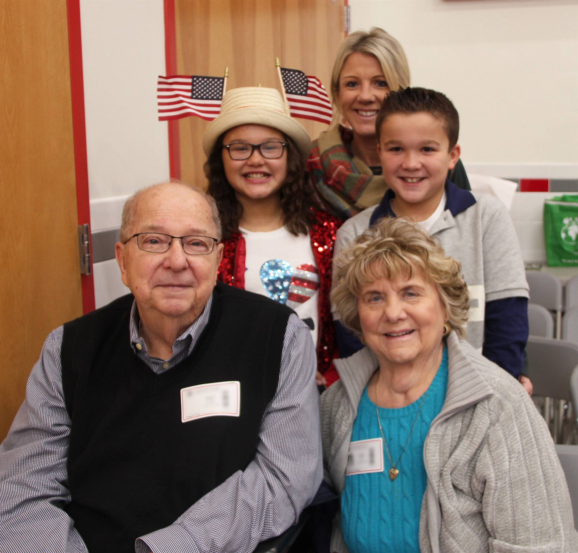 two students with their family with grandpa who is veteran