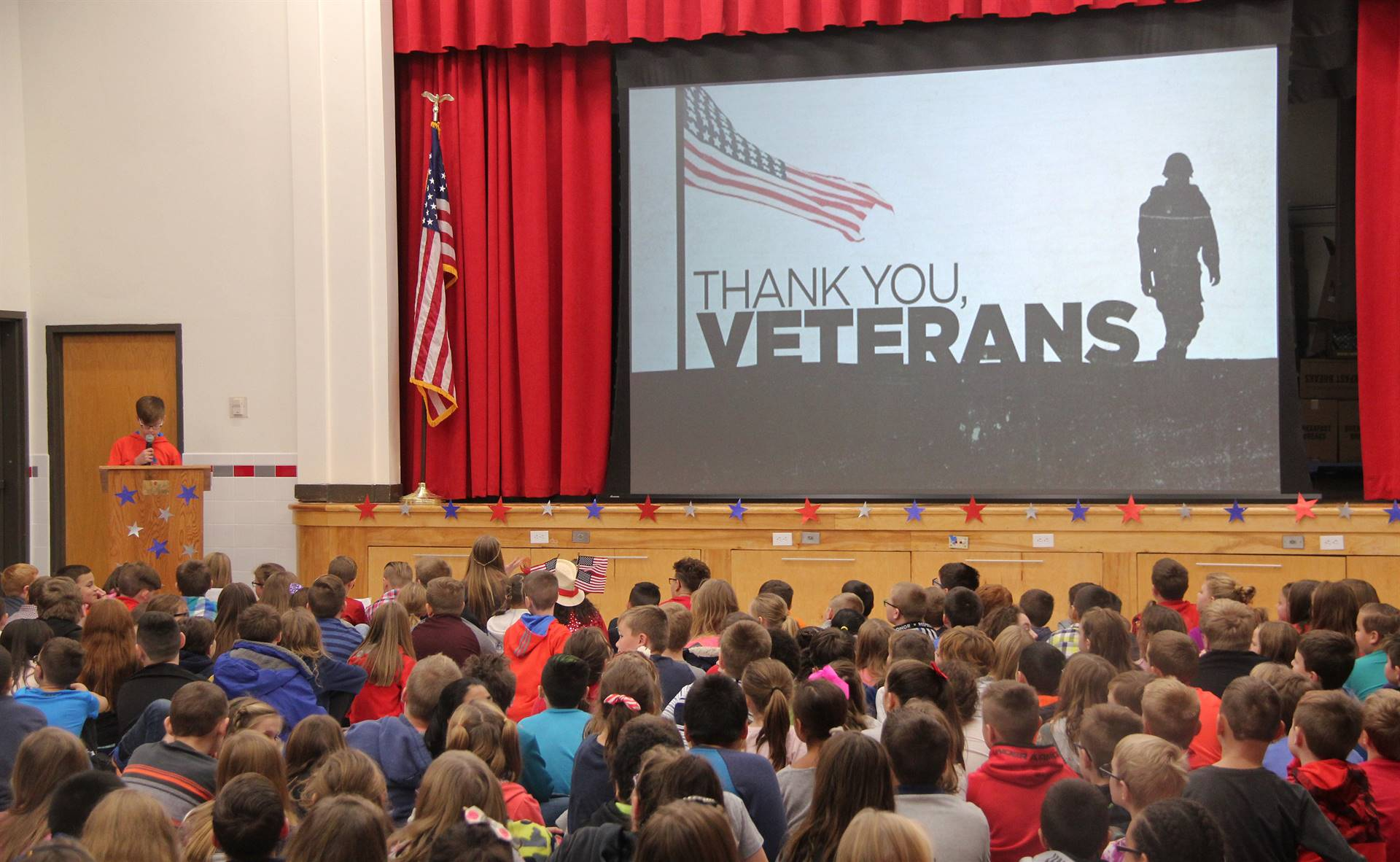 wide shot of student speaking at veterans day assembly