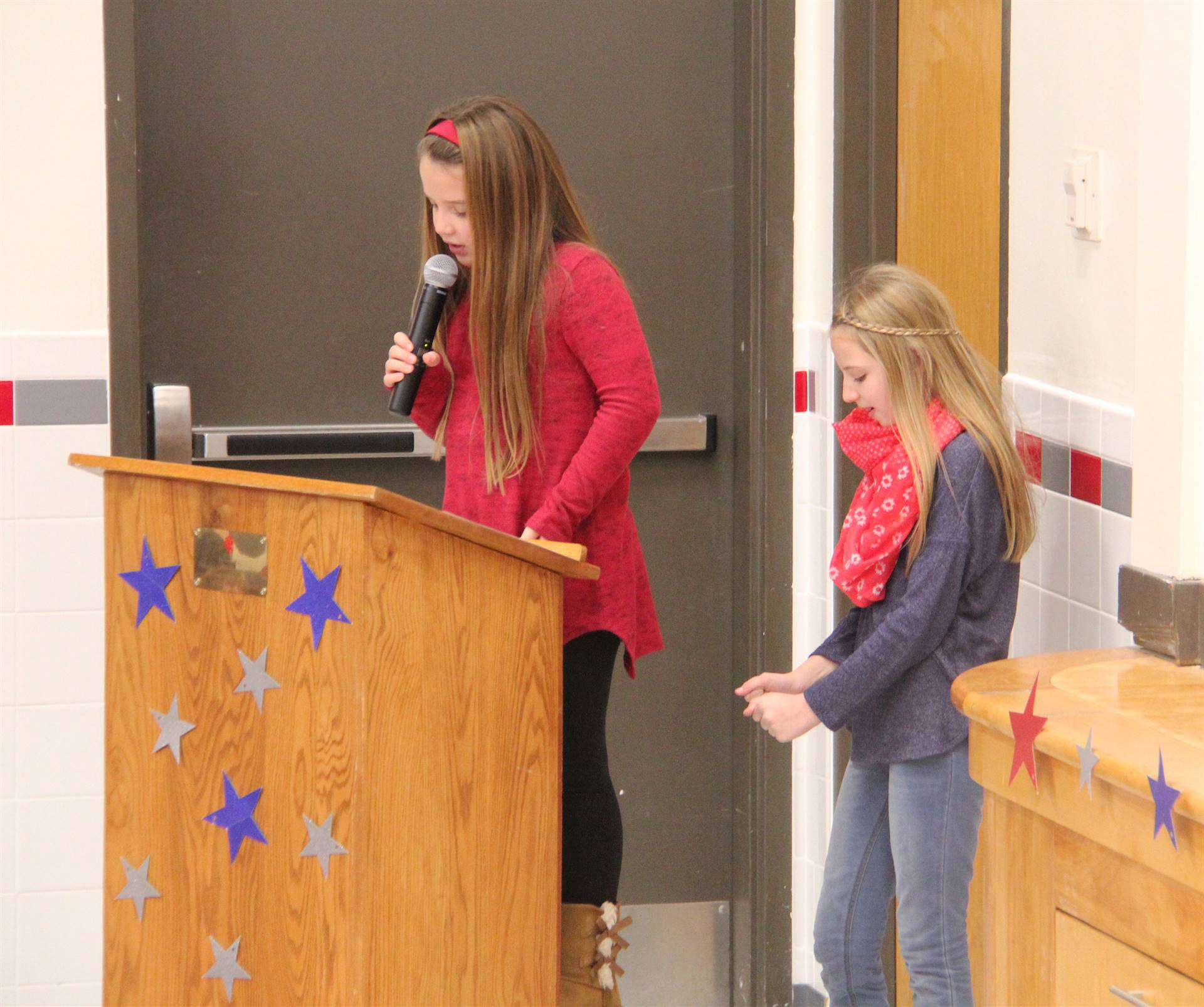 medium shot of student speaking during veterans day assembly