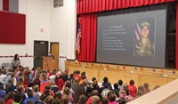 student speaking in front of peers at veterans day assembly