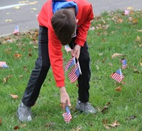 student placing flag in ground