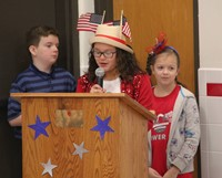 up close of student speaking wearing american flag hat at veterans day assembly
