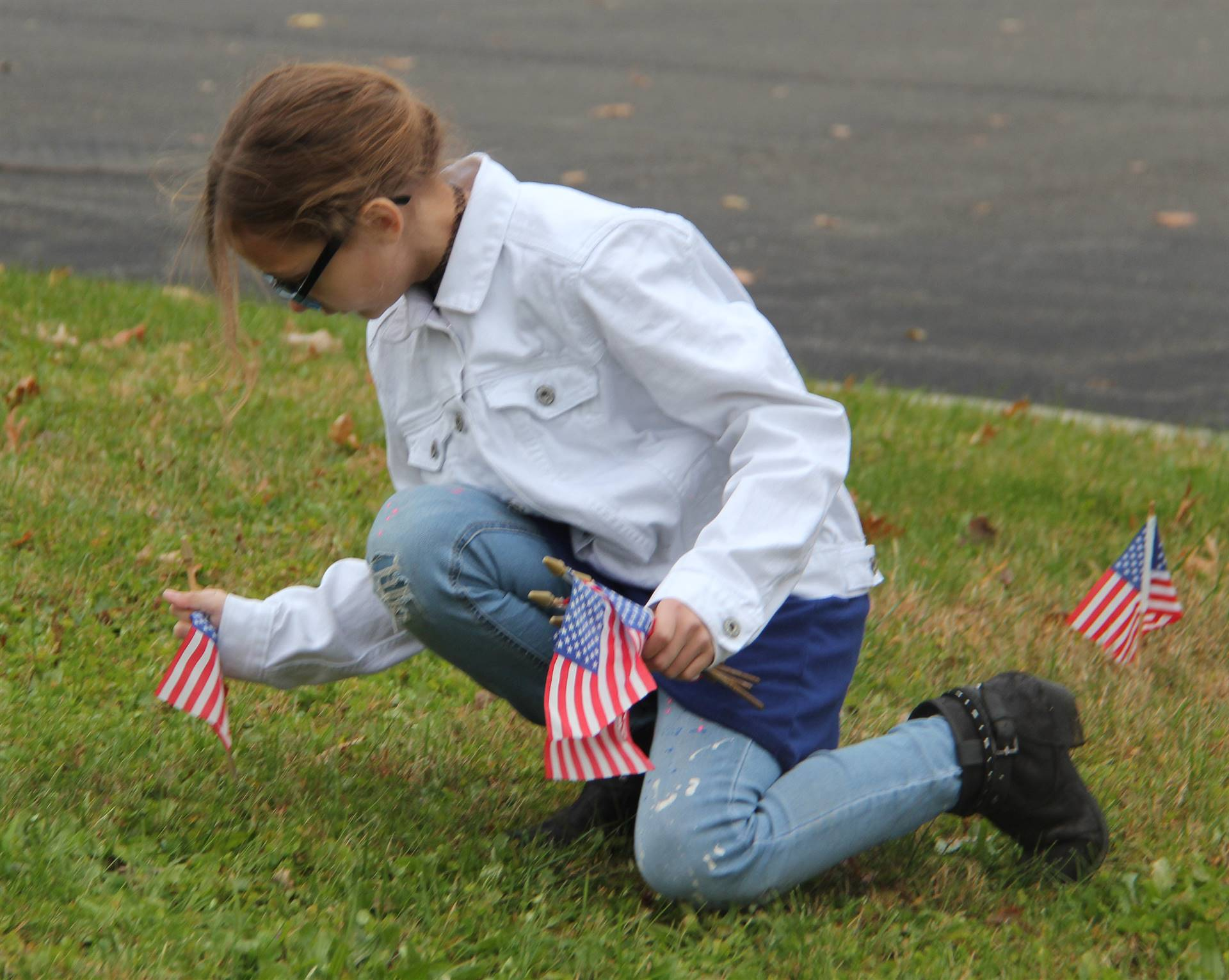 student placing american flag in ground