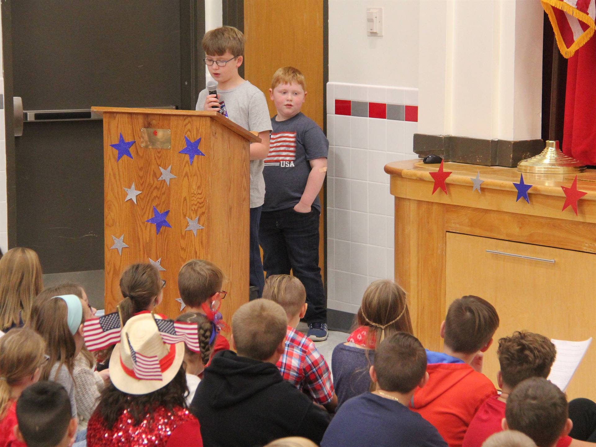student speaking at podium at veterans day assembly