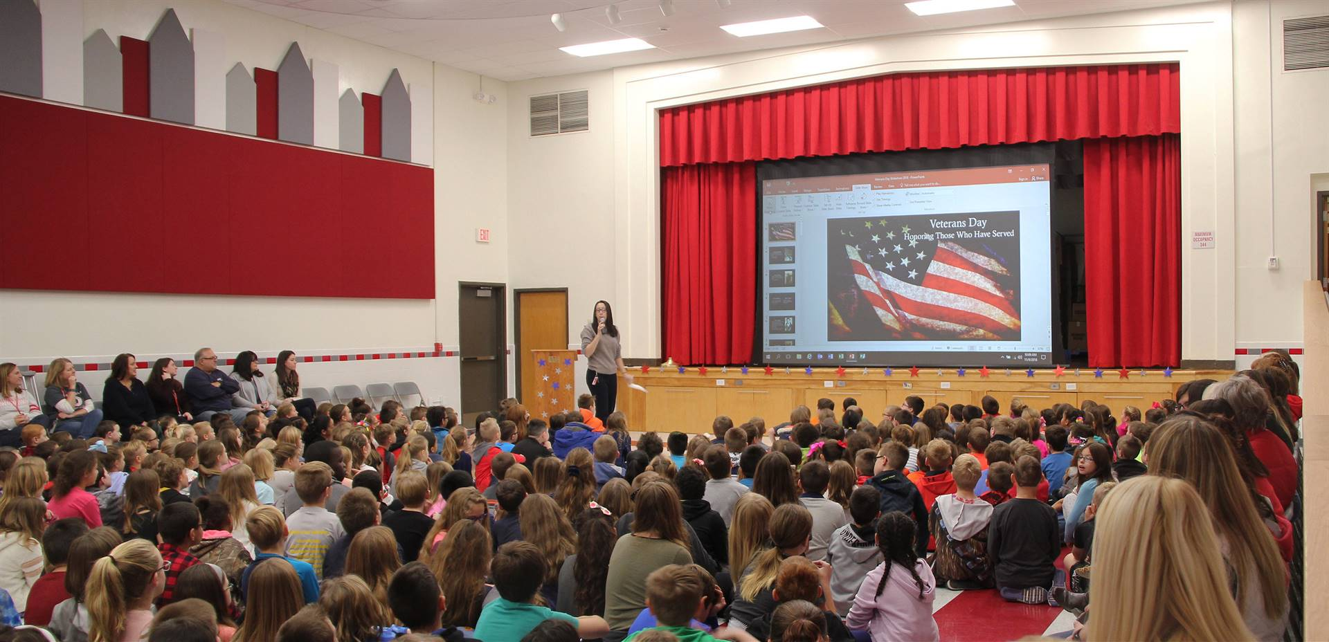 wide shot of teacher speaking at veterans day assembly