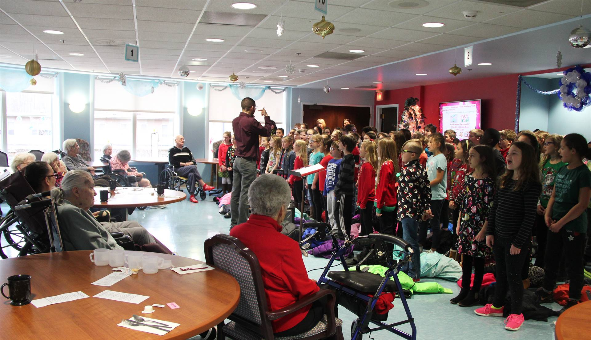 wide shot of students performing for elizabeth church manor residents