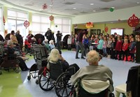 wide shot of students singing for residents