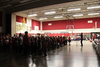 wide shot of students singing in gymnasium
