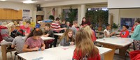 wide shot of classroom of students and teachers in art activity