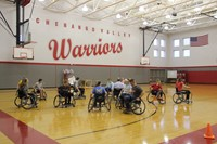 wide shot of students and teachers participating in wheelchair basketball