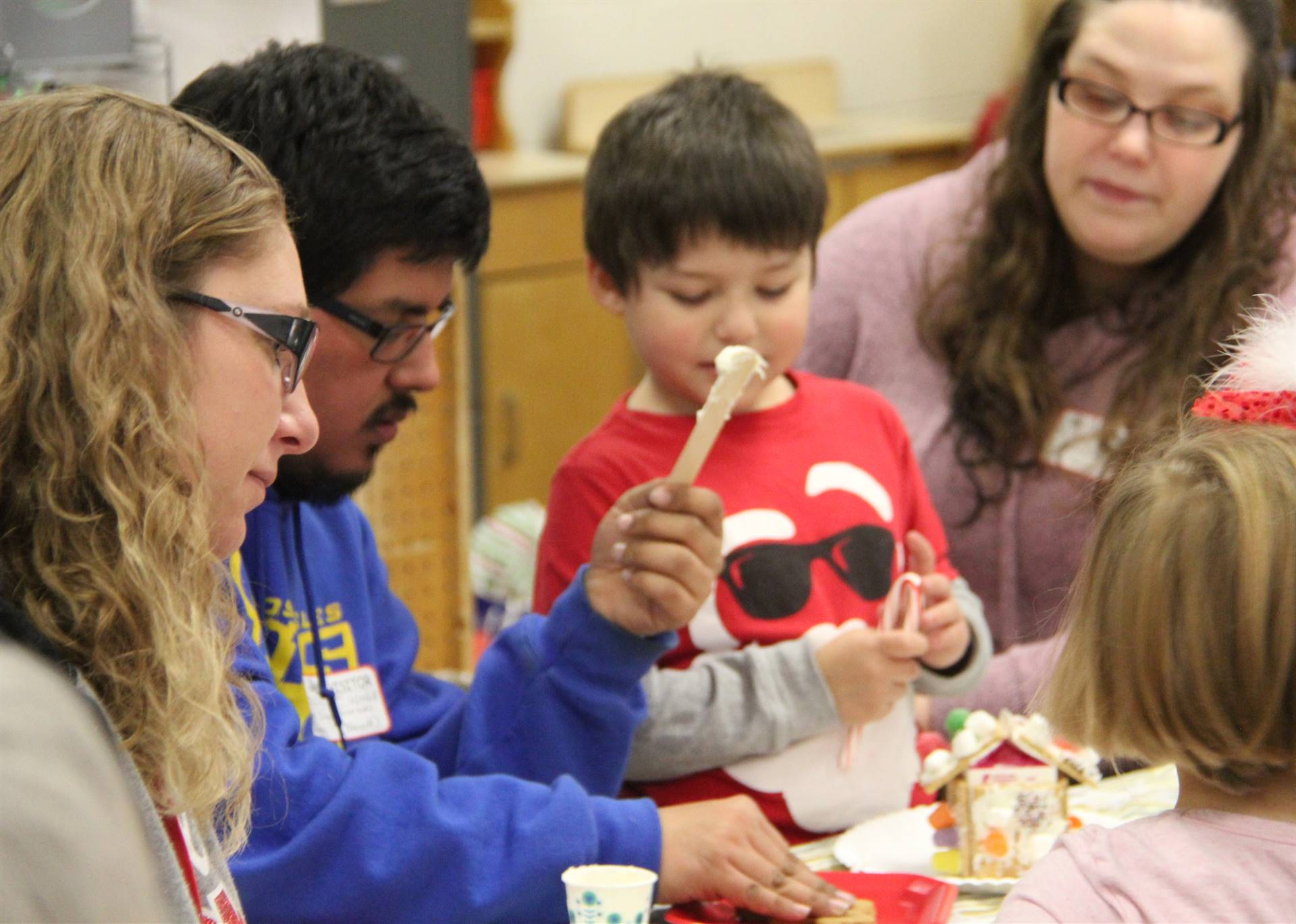 students and adults decorating gingerbread creations