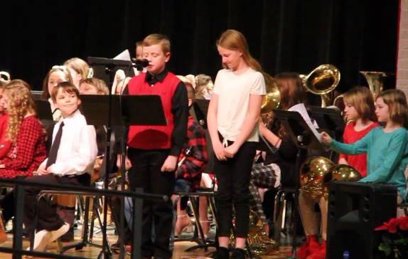 student speaking at podium at winter concert