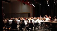wide shot of band students performing from back of stage