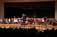 wide shot of band students performing from front of stage