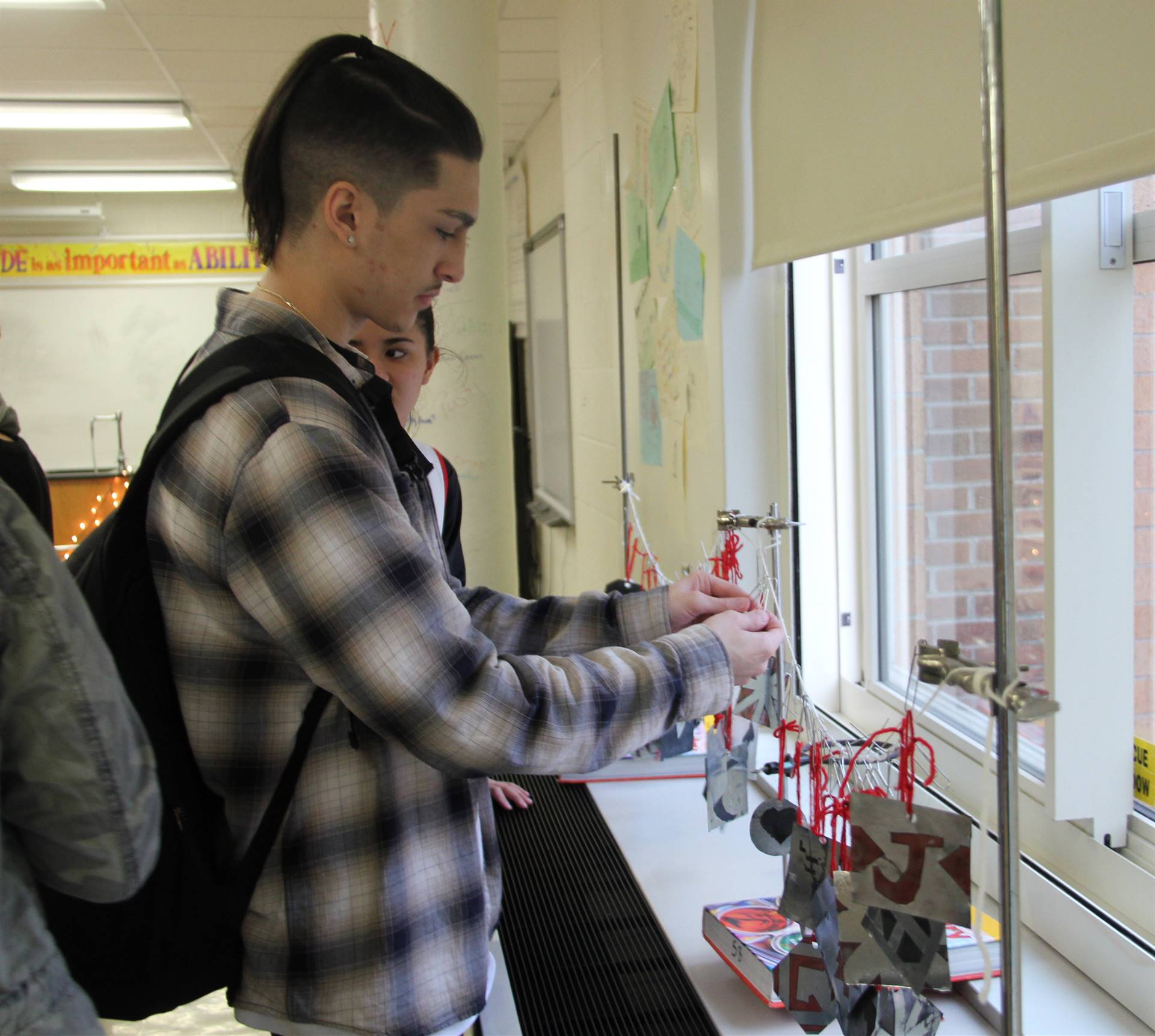 student touching hanging ornaments