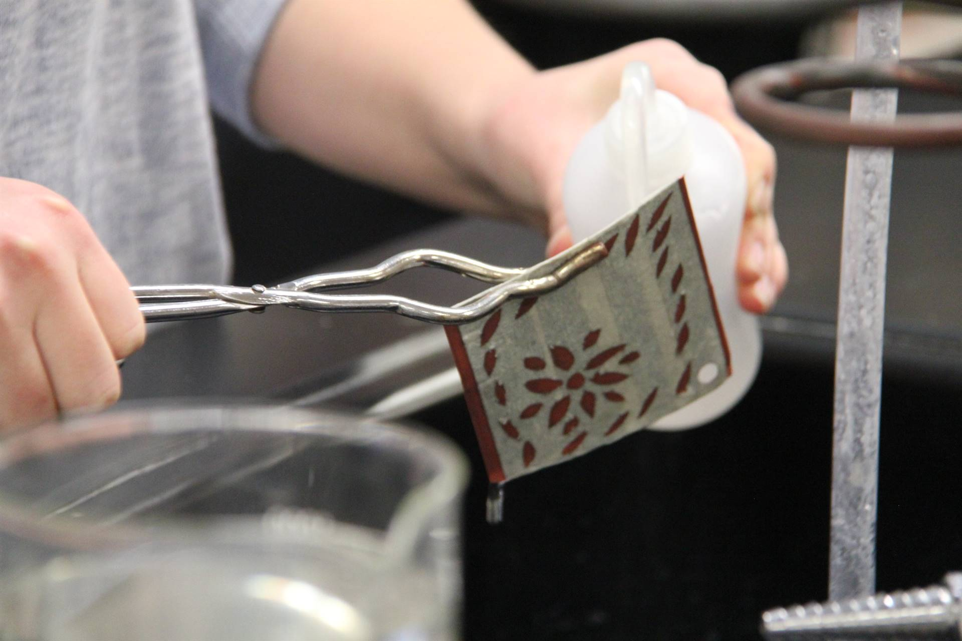 close up of student pouring liquid onto ornament