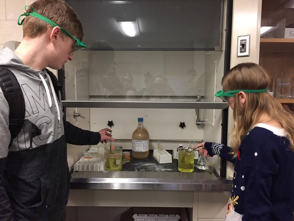 two students putting ornaments in liquid solution