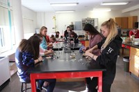 wide shot of students working on copper plating ornaments