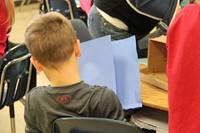 student holding blue paper