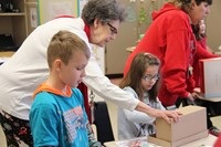 teacher helping student with habitat shoe boxes