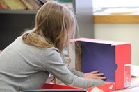 student placing blue paper into shoebox