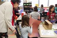 teacher watching student cut brown paper