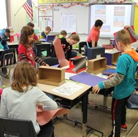 wide shot of students working on habitats in classroom