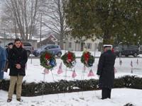 man standing facing wreaths