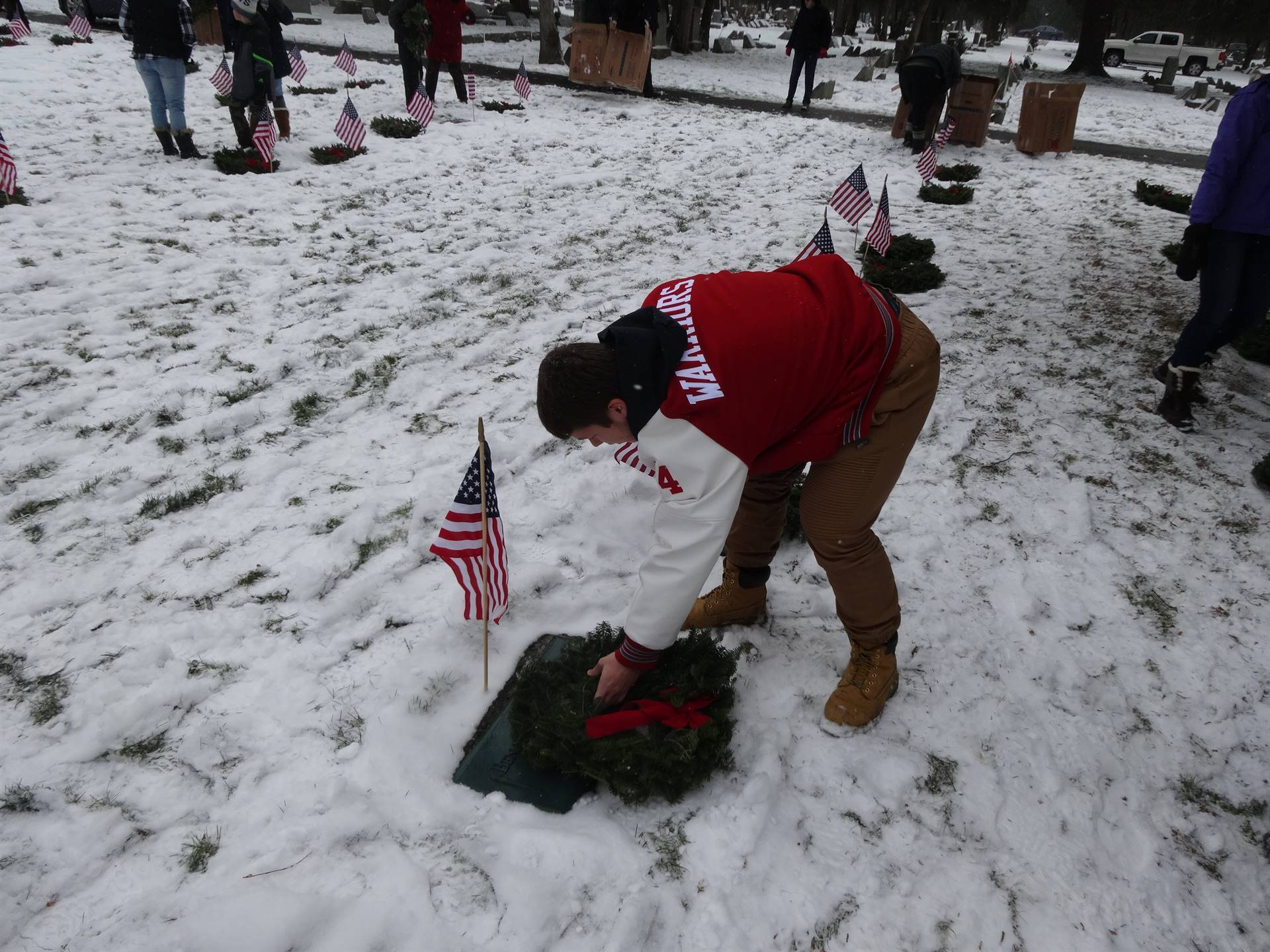 student putting wreath on grave