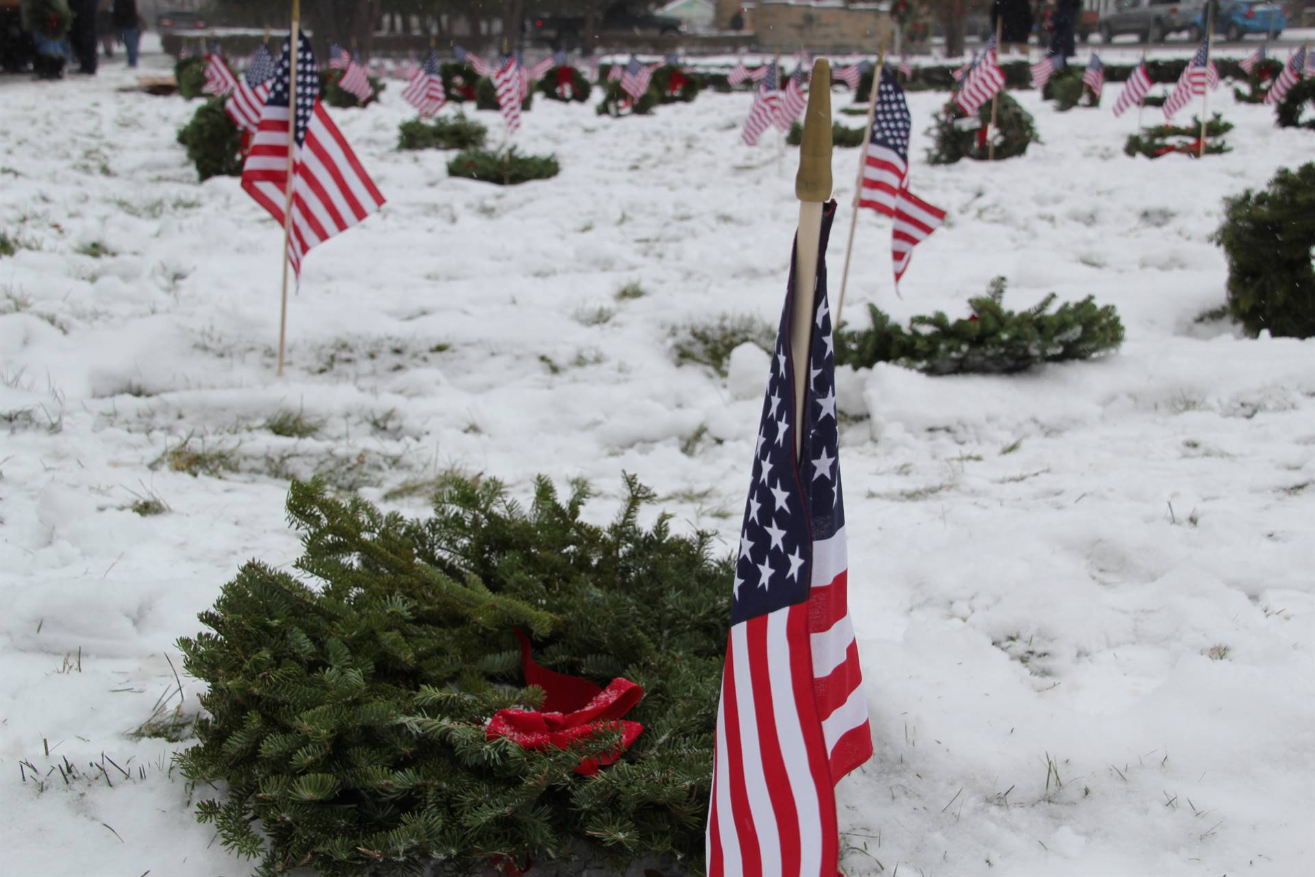 close up of american flag and wreath on grave