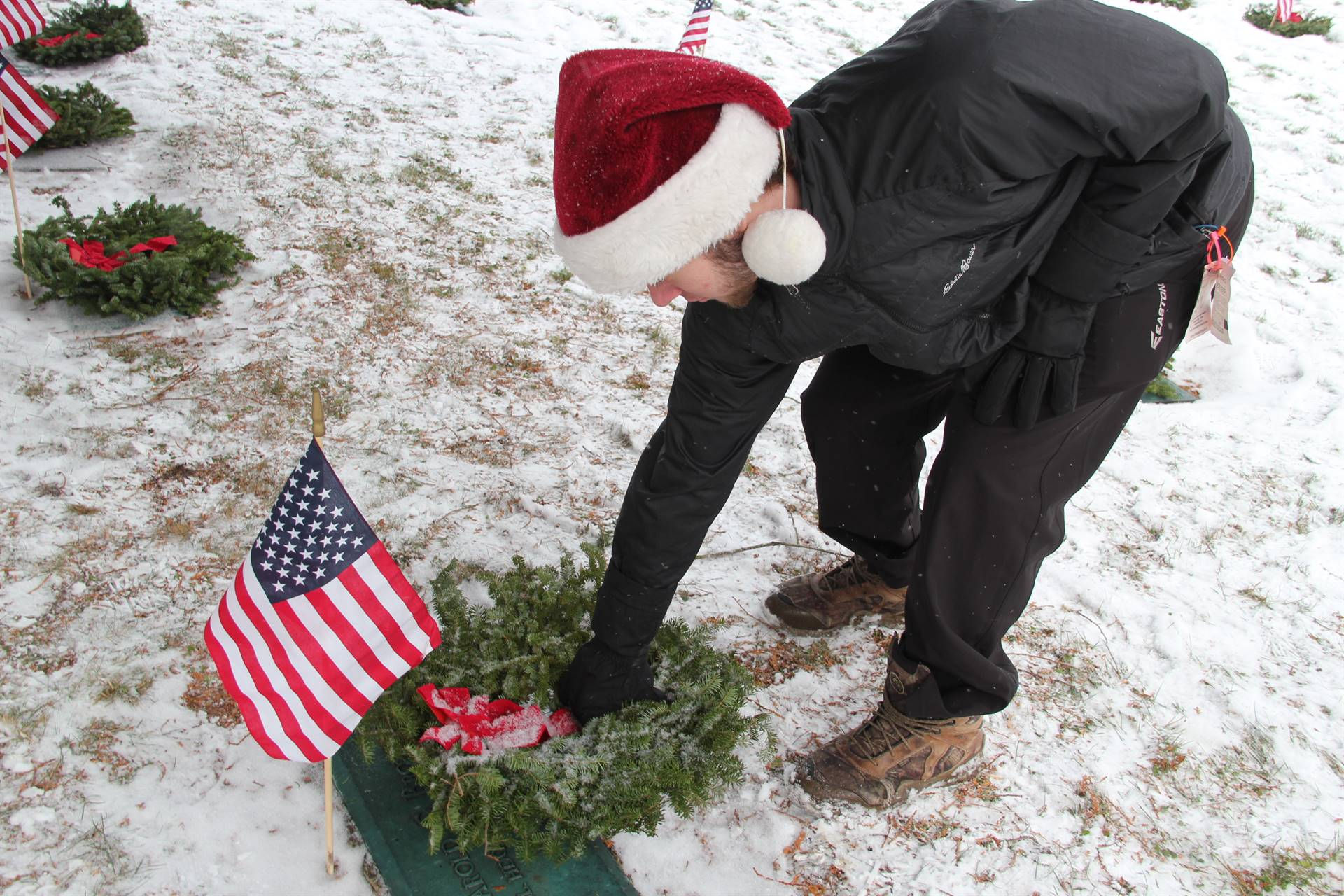 close up of student placing wreath on grave