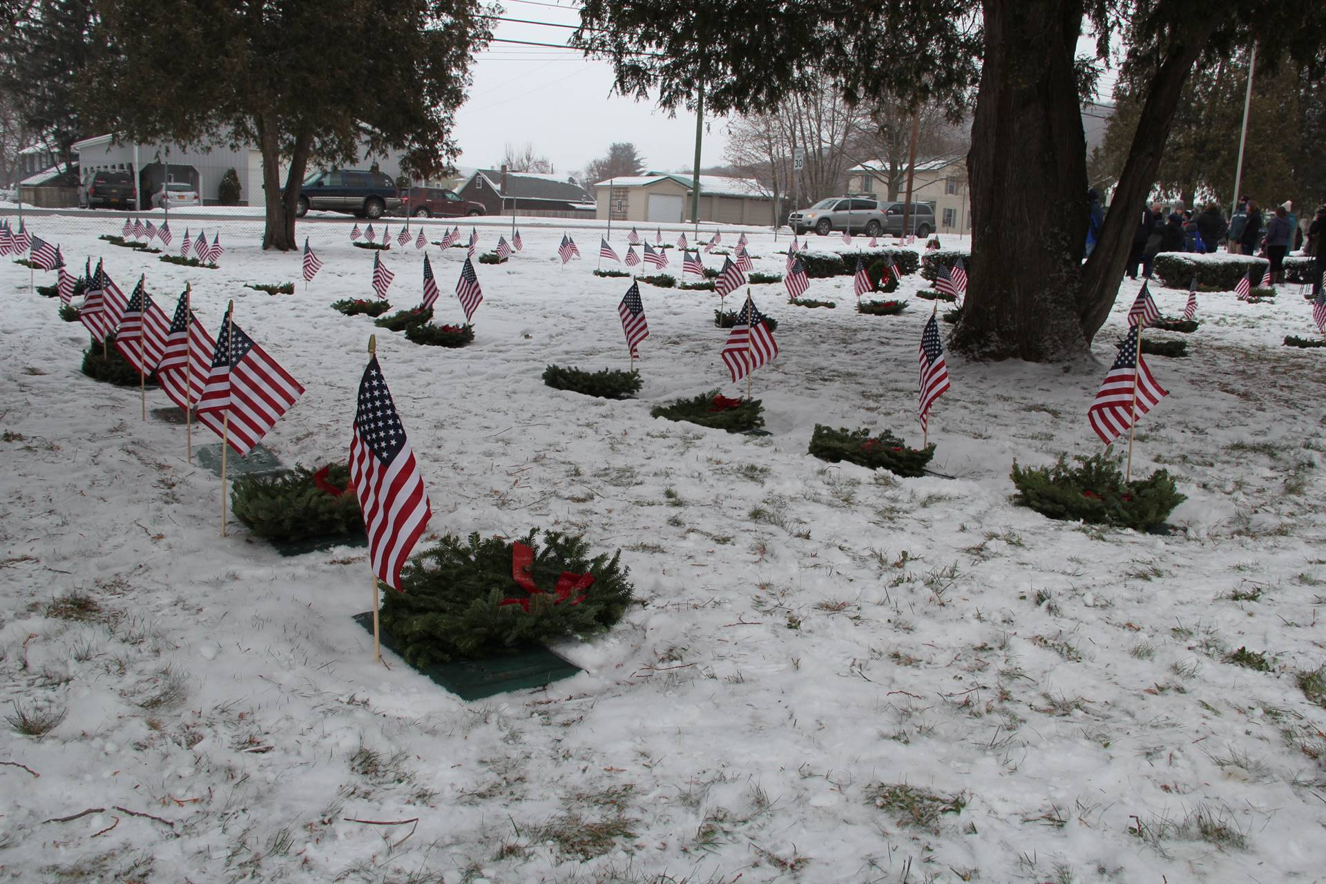 medium shot of graves with people standing in background