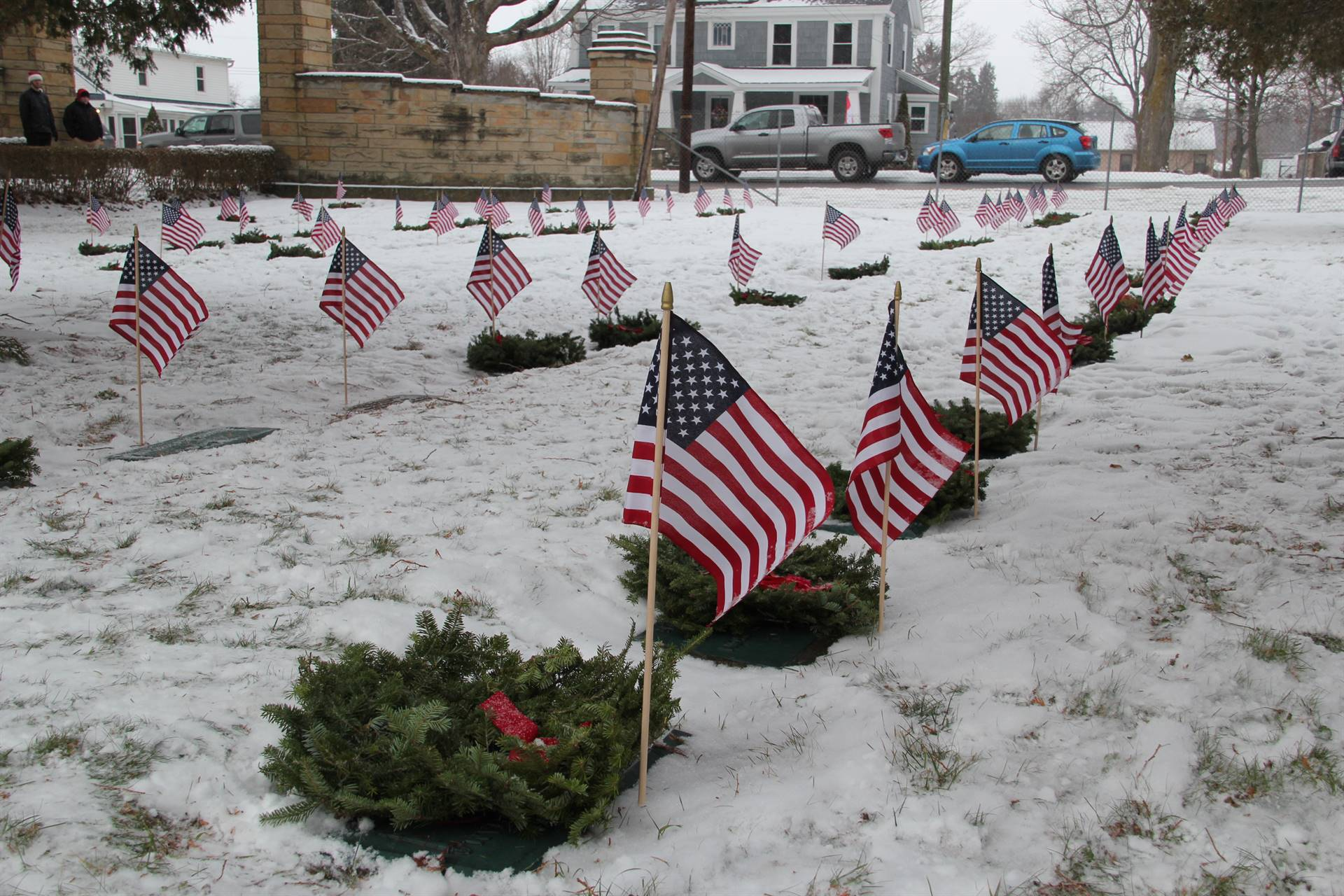 medium shot of line of graves with wreaths and American flags