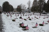 veterans graves with wreaths on them and flags next to them