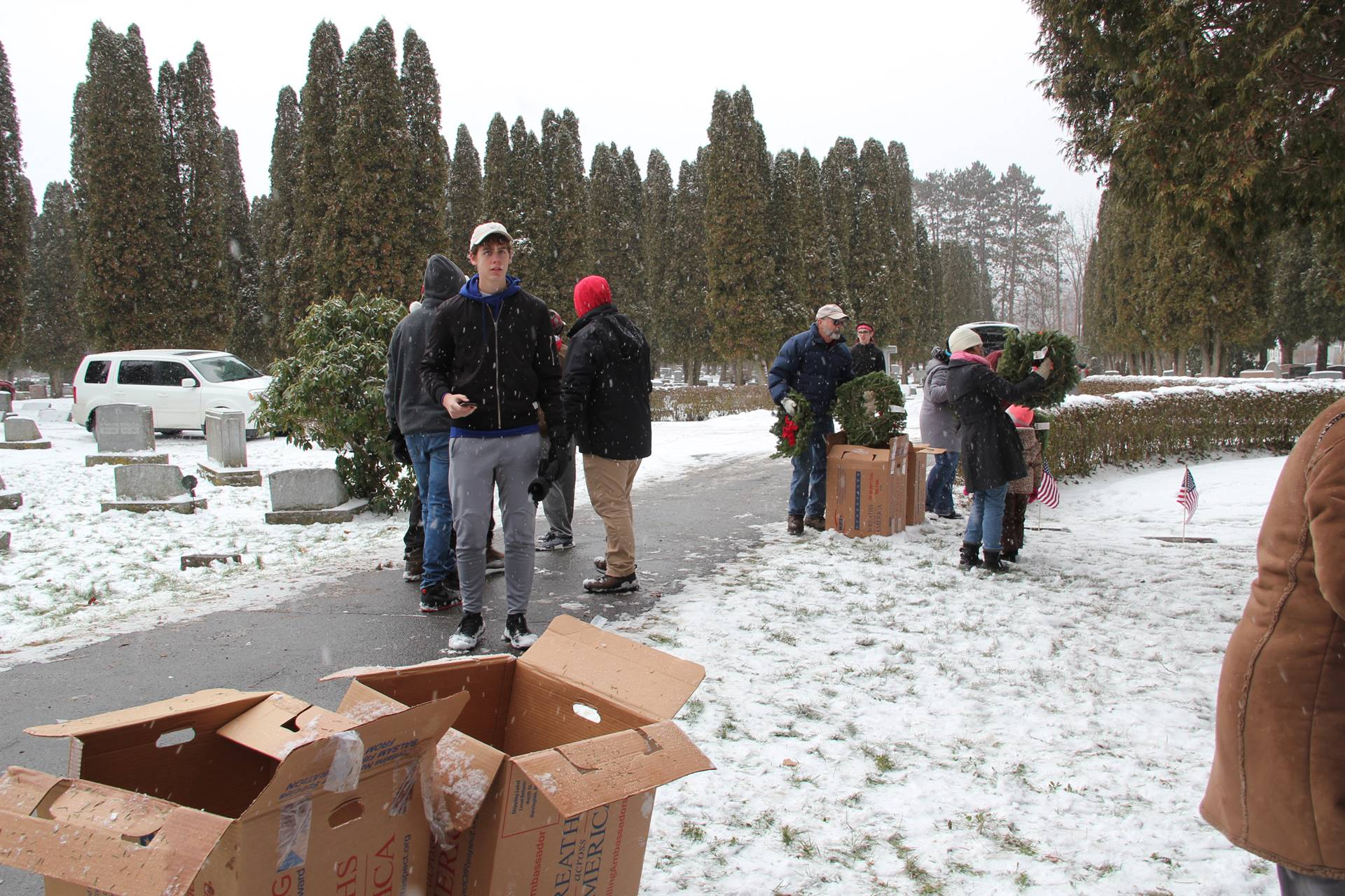 wide shot of cemetary with people standing in background