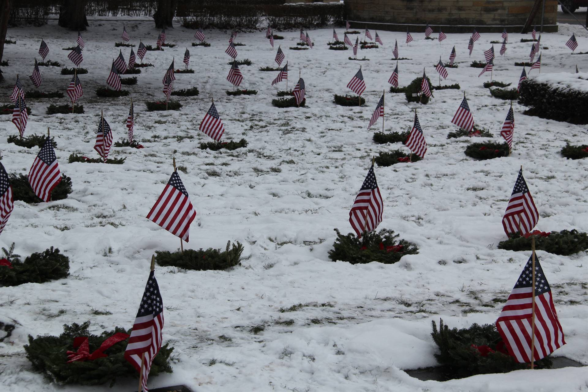 wide shot of people standing and taking wreaths out of boxes