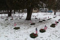 wide shot of wreaths and flags near graves