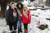 three girl scout members standing next to wreath on grave