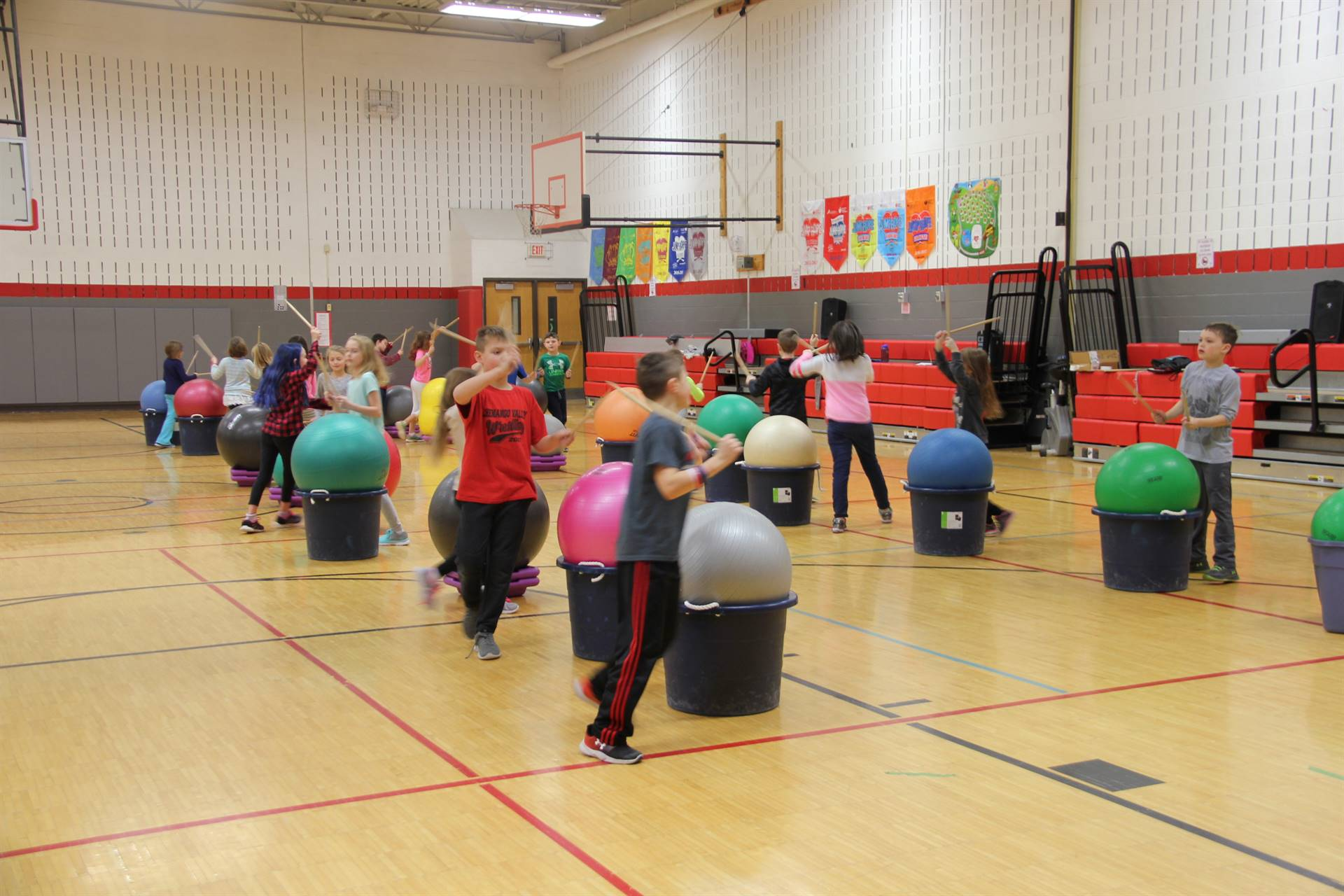 students walking around exercise balls holding drum sticks